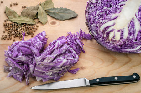 bisected: Chopped and bisected ripe red cabbage, bay leaves and white pepper on a wooden cutting board. Stock Photo