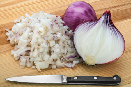 bisected: Bisected and chopped red onion with kitchen knife on wooden board.