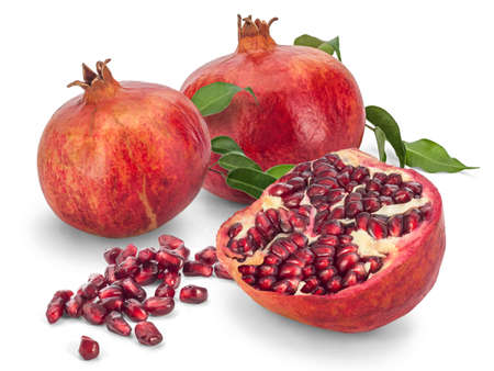punica granatum: Two and a Half Pomegranates (Punica granatum) with scattered seeds, isolated on white background. Stock Photo