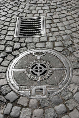 manhole cover: Cast iron storm drain and sewer manhole cover on cobblestone street. Content cyrillic caption: City Sewage B.G.D.. B.G.D. is stands for Belgrade, Serbia