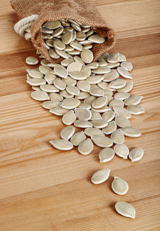 dried gourd: Dried pumpkin seeds spilling from a jute bag on wooden background.