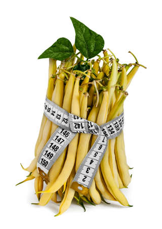 Portion of uncooked Yellow Wax Beans, wrapped with measure tape on white. Stock Photo