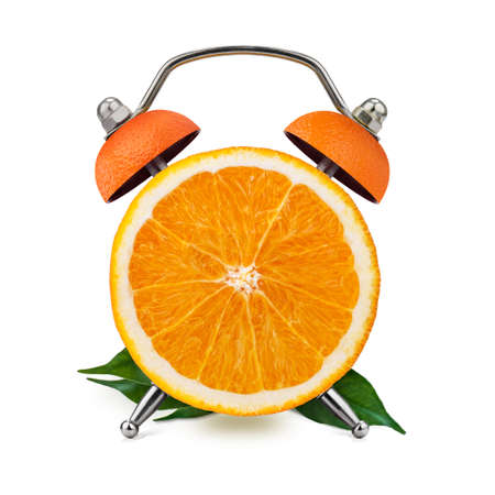 Cut orange, with leaves, as an alarm clock on a white background. Healthy time concept. Banco de Imagens