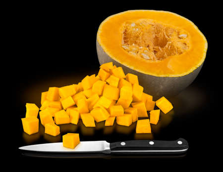 Lumina Pumpkins (Cucurbita maxima Lumina) cross section and cut into cubes with kitchen knife. All on a black background. Not just decorative. Lumina thick orange flesh is good for baking.