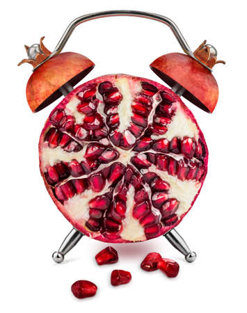 Halved pomegranate, with few scattered seeds, as an alarm clock on a white background. Healthy time concept.