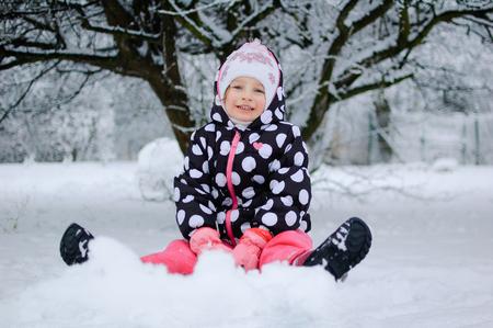 dientes sucios: Una niña que se sienta en la nieve en invierno parque