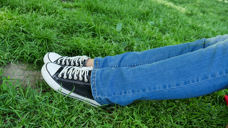 glades: A girl is resting in a clearing. Her legs are visible in sneakers and blue jeans. Rest of the tourist, active way of life, sports shoes, good weekend.