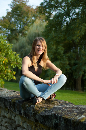 Cute Smiling Young Woman Sitting in the Park During Sunset in Jeans and Black Shirt and Looking at the Camera.