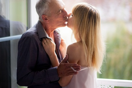 Portrait of Attractive Young Woman Kissing Her Senior Husband near Opened Windows in the Room During Summer Time. Age Difference Concept.