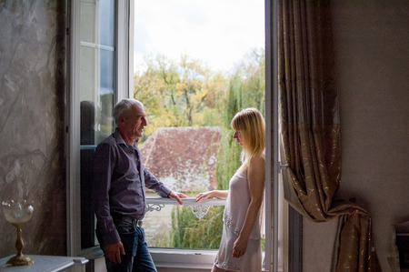 Portrait of Couple with Age Difference Standing near Opened Window inside the House During Summer Sunny Day. Stock Photo