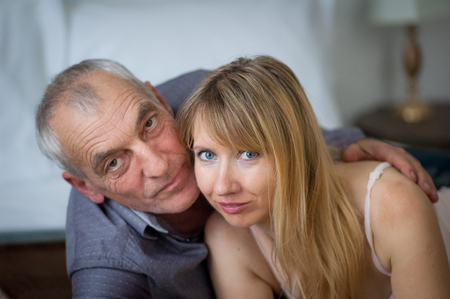 Closeup Portrait of Elderly Man Embracing his Young Wife in Sexy Lingerie Lying in Bed in Their Home. Couple with Age Difference.