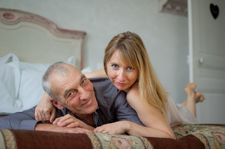 Indoors Portrait of Couple with Age Difference Lying in the Bed.