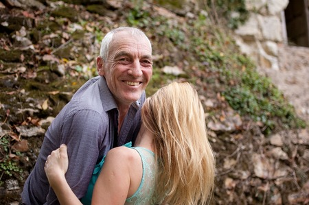 Handsome Senior Man Hugging His Young Girlfriend Outdoors and Smiling Looking at the Camera.