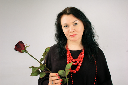 Full Figured Woman in Black Dress and Ethnic Necklace Holding Red Rose on Grey Background in Studio and Looking at the Camera with Sadness