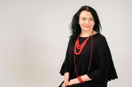 Vollfigurige Frau im schwarzen Kleid und in der roten ethnischen Halskette, die auf dem Stuhl im Studio sitzt, kopieren Sie Raum auf der linken Seite des Fotos