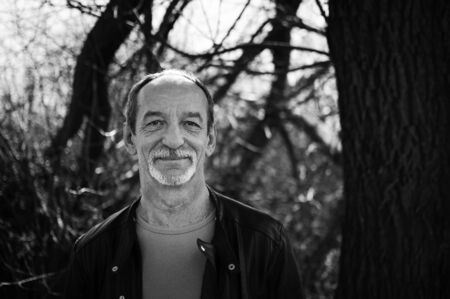 Black and white portrait of mature serious man with grey hair in dark leather jacket standing outdoors near the tree on sky background. Stok Fotoğraf