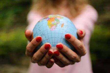 The girl in a pink sweater with red manicure holds a small globe with geographical names in Ukrainian cyrillic letters on it. African continent and Ocean are visible.