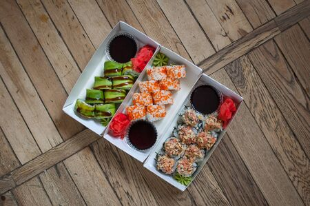 Japanese cuisine. Sushi set on a tree carton box over wooden background. Food for take away or sushi delivery concept
