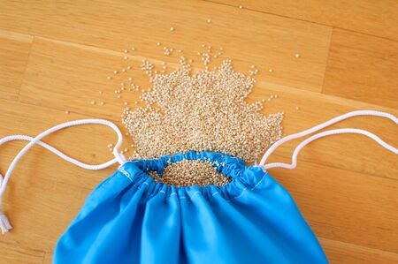 White quinoa seeds in transparent blue reusable bag on wooden background. Vegetarian food concept