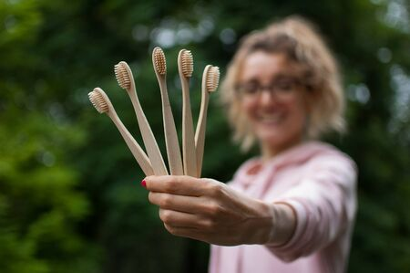 Young beautiful woman with blonde curly hair in pink hipster jacket and eyeglasses holding five bamboo toothbrushes in hand. Zero waste concept