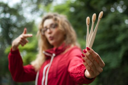 Portrait of blonde girl with hipster eyeglasses in dark red jacket holding a useful bamboo toothbrushes outdoors in the urban park. Green living and zero waste concept Stock Photo