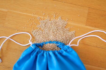 Top view of white quinoa seeds in blue reusable package on wooden background. Healthy eating concept