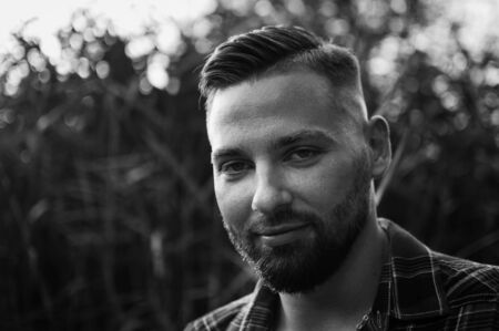 Black and white portrait of young bearded man looking at the camera outdoors in the park on trees background Stock Photo