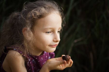 Beautiful little blond girl in violet dress with ponytail is eating a chocolate candy in the park durring a day, sugar addiction concept