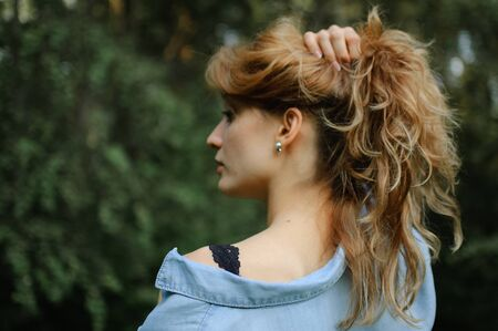 Side view portrait of sexy blonde girl with curly hair wearing blue casual jeans blouse and black lingerie posing in the park on green trees background. Hipster style concept. Archivio Fotografico - 133373909