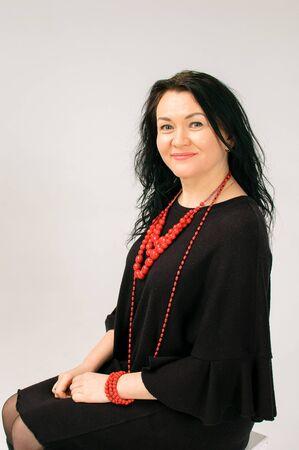 Plus Size Model in schwarzem Kleid und roter ethnischer Halskette Sitzen auf dem Stuhl im Studio, kopieren Sie den Platz auf der linken Seite des Fotos
