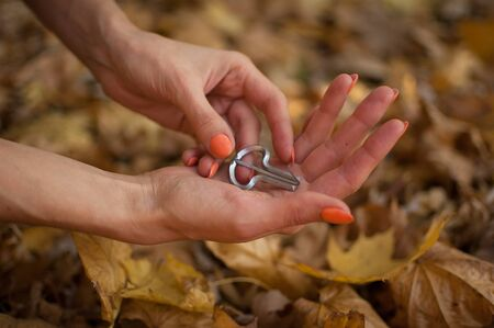 Female hands are holding traditional hutsul drymba or jews-harp, the oldest musician instrument in the world on fallen leaves background during autumn day outdoors Foto de archivo
