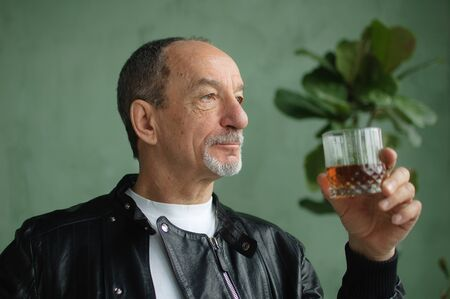 Side view of senior man holding glass of whisky or brandy and thinking about something in loft style room with light green walls and houseplants on background. Alcohol addiction