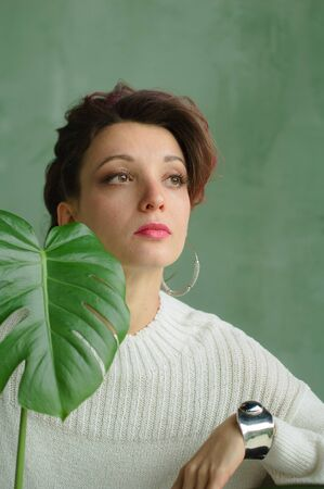 Beauty portrait of sensual brunette girl with dark pink hair and white sweater holding a green spring plant. Beauty, natural cosmetics concept.