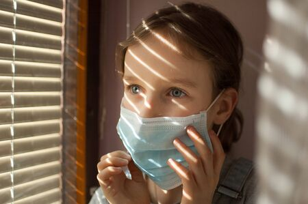 Little girl is sitting on the windowsill and trying to put protective disposable mask on her face during self-isolation at home because of Coronavirus Covid-19 on blinds background