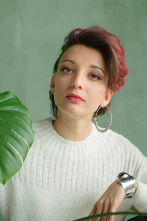 Beautiful lady in white sweater, silver earrings, and braclet sitting near green palm tree and looking at camera with tenderness. Beauty and fashion concept