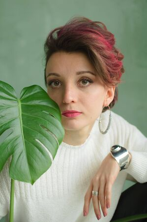 Portrait of a young beautiful woman with perfect smooth skin with a large green tropical leaf. Fashion, beauty, makeup, cosmetics, health, ecology, nature, spa, wellness.