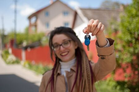 Cute smiling girl with long dreadlocks and eyeglasses showing bunch of house keys in a hand towards the camera. Real estate agent concept Archivio Fotografico