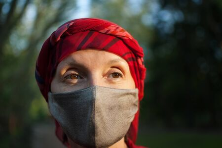 Mature woman wearing handmade textile face mask as accessory and protective element during sunny spring day in the park because of coronavirus pandemic Archivio Fotografico