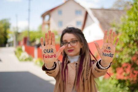 Young girl with long dreadlocks and eyeglasses in nude color trench is showing hands with written slogan Our future in our hands on some building background. Positive psychology concept Archivio Fotografico