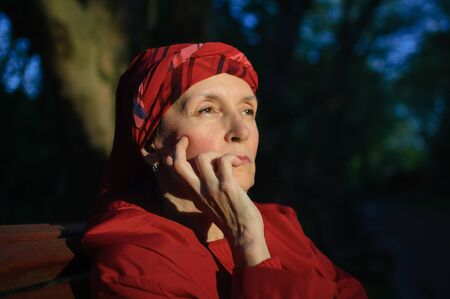 Female portrait of mature woman dressed in red clothes and sitting on the bench and enjoying a good weather and sunset in the park during a spring or autumn.