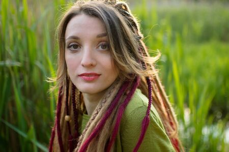Outdoors portrait of a girl with dreadlocks and green shirt in a city park near the lake during a sunset, be free concept. Archivio Fotografico
