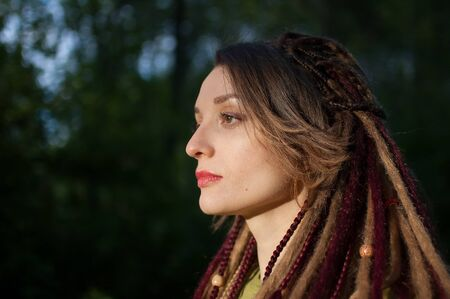 Outdoors portrait of a sensual girl with long dreadlocks wearing green shirt in a city park during a sunset, be different, alternative people concepts