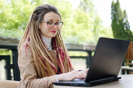 Smiling successful female copywriter with long dreadlocks casual dressed is using black laptop and 4g or 5g connection while enjoying a coffee and working remotely