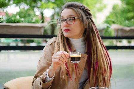 Positive smart student girl with long dreadlocks is resting in a street coffee shop with transparent cup of espresso.