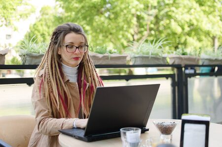 Charming female entrepreneur in eyeglasses with long dreadlocks casual dressed is planning a working process using application on laptop device while sitting in modern street cafe outdoors