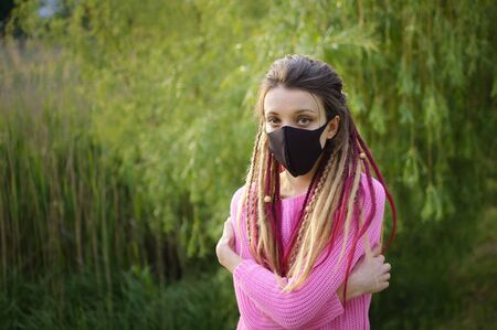 Modern girl with dreadlocks wearing textile mask on her face to protect herself from Coronavirus Covid-19 spending a time in the park outdoors Archivio Fotografico