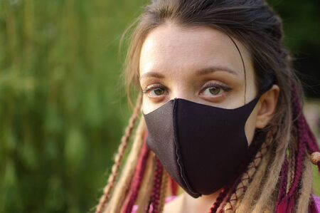 Modern girl with dreadlocks wearing textile mask on her face to protect herself from Coronavirus Covid-19 spending a time in the park outdoors Stok Fotoğraf