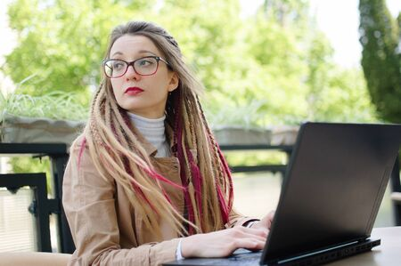 Outdoors portrait of beautiful talented smart student with long dreadlocks is preparing for upcoming examinations while sitting in coffee shop outside.