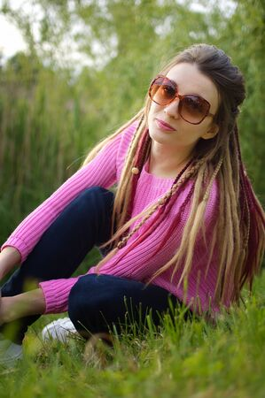 Outdoors portrait of a girl with dreadlocks wearing pink sweater and sunglasses in a city park during a sunset, be free concept.