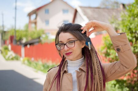 Modern young girl with long dreadlocks and eyeglasses is showing bunch of house keys in a hand towards the camera. Real estate agent concept Archivio Fotografico